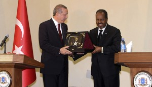 Turkey's President Tayyip Erdogan (L) receives a gift from Somalia's President Hassan Sheikh Mohamud (R) after addressing a joint news conference in Somalia's capital Mogadishu January 25, 2015. Turkish President Tayyip Erdogan travelled to the Somali capital Mogadishu under heavy security on Sunday, making his second visit in four years to promise further investment in the country as it struggles to rebuild after two decades of conflict. REUTERS/Feisal Omar (SOMALIA - Tags: POLITICS) - RTR4MTPA